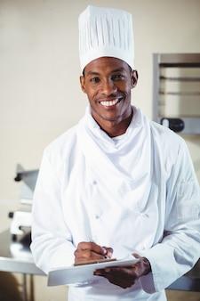 Retrato del chef sonriente haciendo notas en un portapapeles