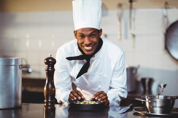 Retrato del chef sonriente preparando una ensalada