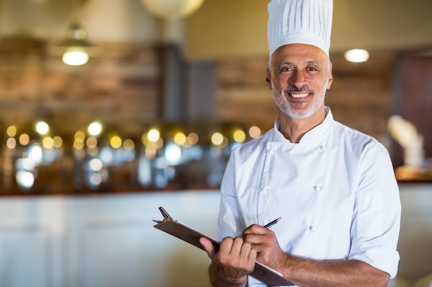 Retrato del chef sosteniendo un portapapeles