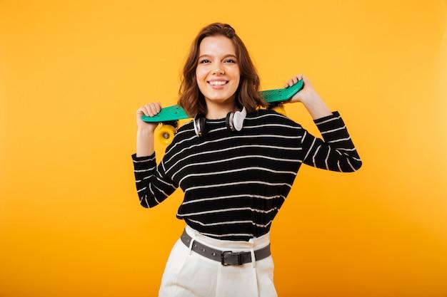 Retrato de una chica alegre con patineta