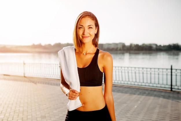 Retrato de una chica atlética. modelo de fitness deporte joven hermosa preparándose para correr en el parque de la ciudad.