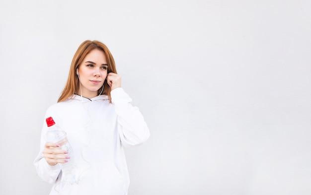 Retrato de una chica atractiva deportiva sobre un fondo blanco, sosteniendo una botella de agua