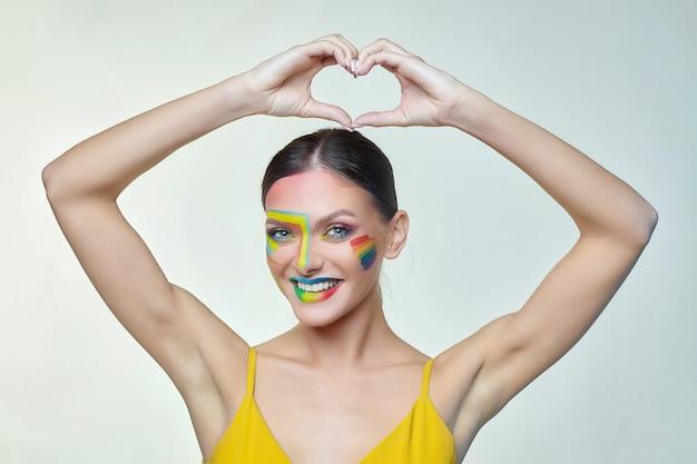 Retrato de una chica atractiva con maquillaje brillante, cuyas manos tomaron la forma de un corazón