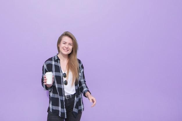 Retrato de una chica atractiva de pie sobre un fondo morado con una taza de papel en sus manos y mirando a la cámara.