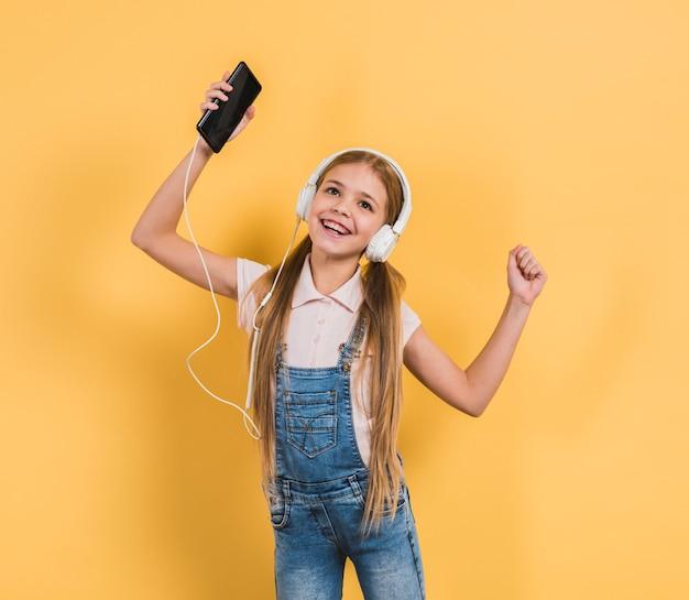 Retrato de una chica bailando mientras escucha música en el auricular a través del teléfono móvil con fondo amarillo