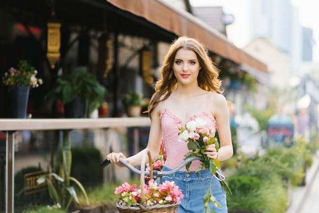 Retrato de una chica bonita y hermosa en la calle de la ciudad, bañada por la puesta de sol. la niña sostiene un ramo de rosas y sostiene un manillar de bicicleta. el concepto de paseos veraniegos