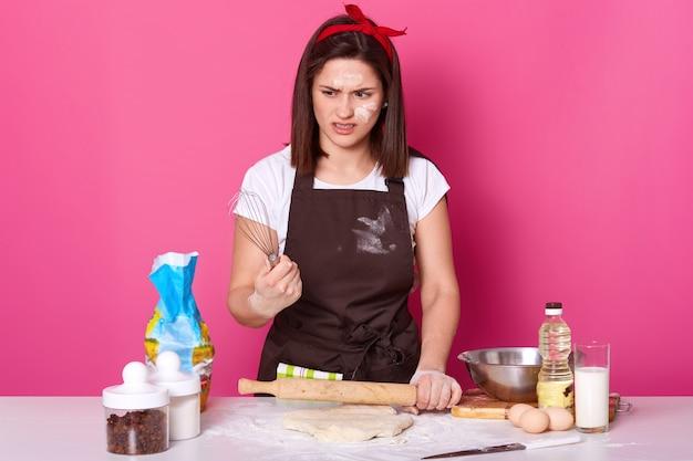 Retrato de una chica de cabello oscuro con un delantal manchado de harina, una camiseta y una banda roja para el cabello, se para con el batidor en las manos y se siente asqueada por los pasteles horneados, quiere descansar. baker hace deliciosas galletas.
