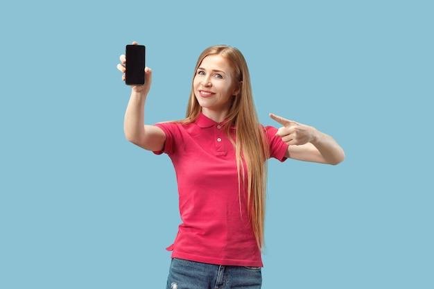 Retrato de una chica casual confidente que muestra la pantalla en blanco del teléfono móvil aislado sobre fondo azul.