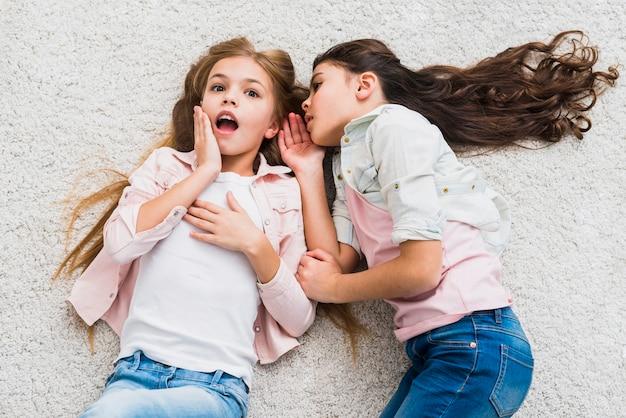 Retrato de una chica chismosa contando un secreto en el oído a su amiga tendida en la alfombra