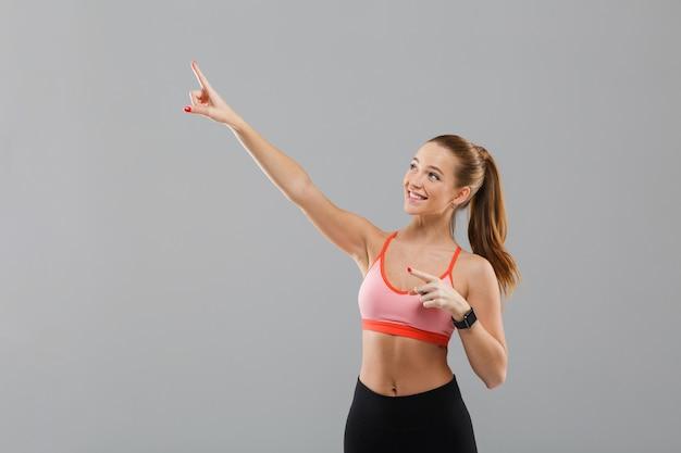 Retrato de una chica deportiva bastante joven señalando