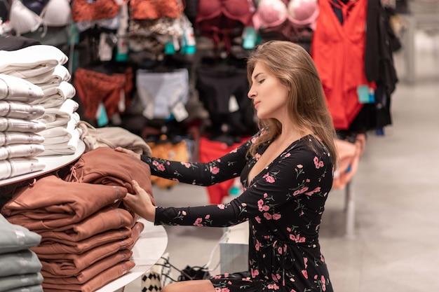 Retrato de una chica elegante en perfil posando medio sentado cerca del estante con cosas y selecciona la ropa de la pila de cosas propuesta. venta. compras. dia de descuentos.