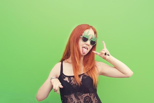 Retrato de una chica con estilo loca que muestra gesto de rock en verde