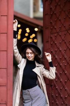 Retrato de una chica guapa vestida con ropa de otoño cerca de la antigua puerta vintage