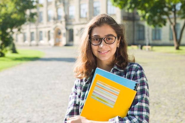 Retrato de una chica linda estudiante en vasos con libros.