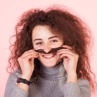 Retrato de chica morena divertida sobre fondo rosa