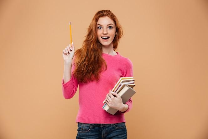 Retrato de una chica pelirroja bonita emocionada sosteniendo libros y tener una idea