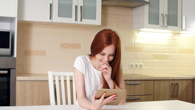 Retrato de una chica pelirroja con un tablet pc en la cocina