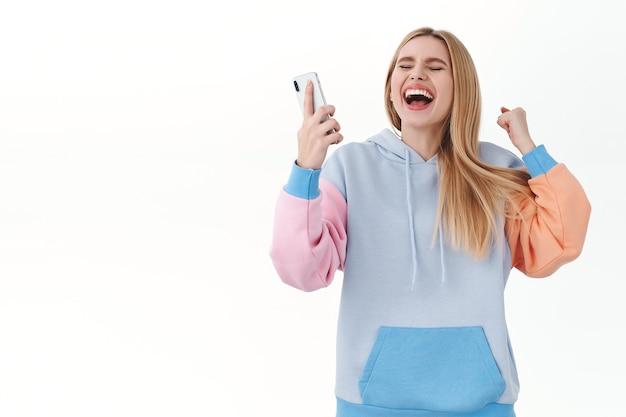 Retrato de una chica rubia alegre y entusiasta que gana la competencia en línea, levanta las manos en la bomba del puño, grita sí o hurra