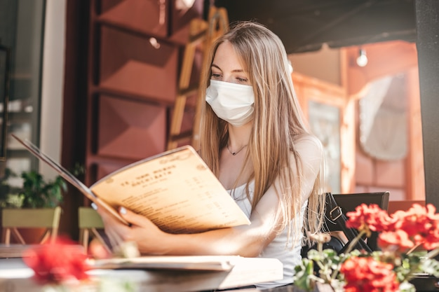 Retrato de una chica rubia con una máscara médica protectora sentado en una mesa en un café