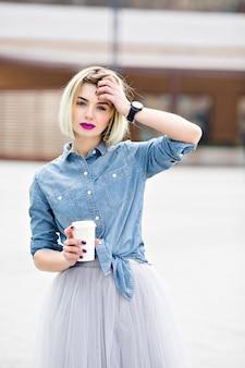 Un retrato de una chica rubia soñadora de pie con labios rosados brillantes sosteniendo una taza de café y sosteniendo una mano cerca de su cabeza