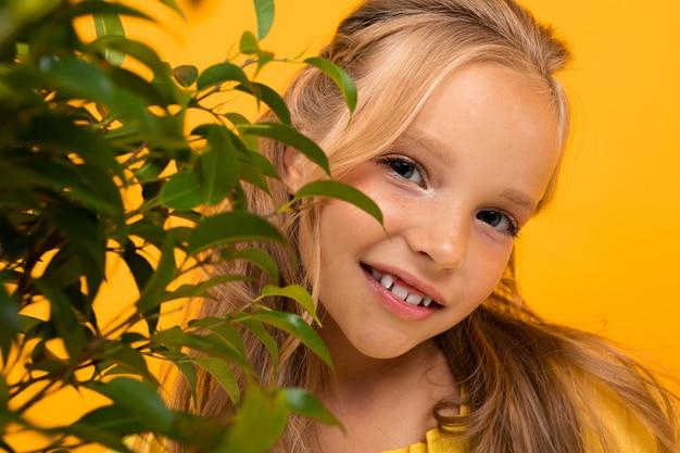 Retrato de una chica rubia y sonriente con hojas de plantas en una pared naranja