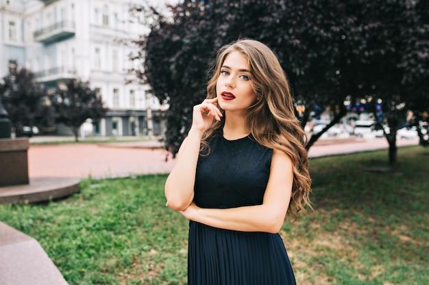 Retrato de chica seria y elegante en el parque de la ciudad. tiene cabello largo, vestido negro, labios vinosos y se ve con nostalgia.