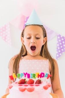 Retrato de una chica sorprendida mirando su hermoso pastel de cumpleaños