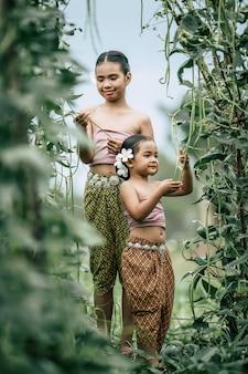 Retrato de chicas encantadoras en traje tradicional tailandés y poner flor blanca en su oreja, de pie en el patio de la planta de frijoles largos, sonríen con felicidad