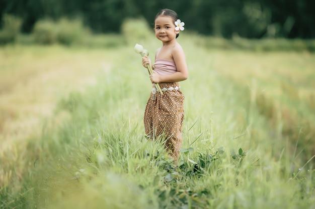 Retrato de chicas encantadoras en traje tradicional tailandés y poner flor blanca en su oreja, de pie y sosteniendo dos loto en la mano en el campo de arroz, sonríe con felicidad, copia espacio