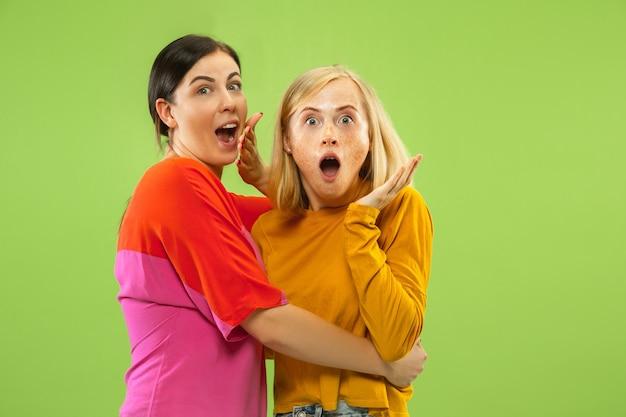 Retrato de chicas muy encantadoras en trajes casuales aislados en el espacio verde. dos modelos femeninas como novias o lesbianas
