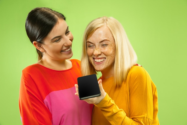 Retrato de chicas muy encantadoras en trajes casuales aislados en el espacio verde. novias o lesbianas hablando por teléfono inteligente