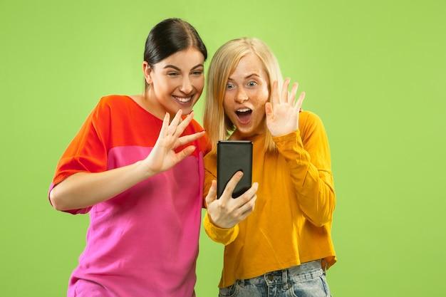 Retrato de chicas muy encantadoras en trajes casuales aislados en la pared verde. novias o lesbianas haciendo selfie. concepto de lgbt, igualdad, emociones humanas, amor, relación.
