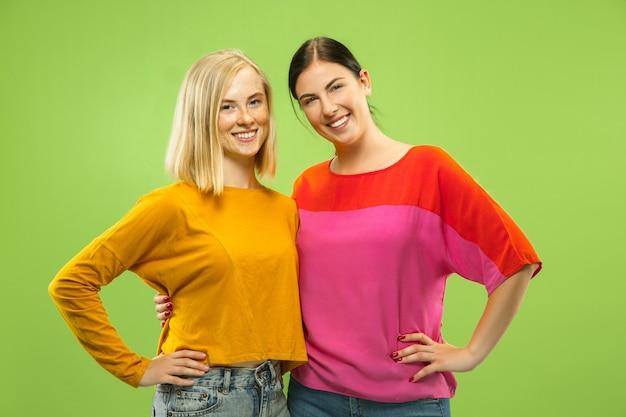 Retrato de chicas muy encantadoras en trajes casuales aislados sobre fondo verde de estudio. dos modelos femeninas como novias o lesbianas. concepto de lgbt, igualdad, emociones humanas, amor, relación.