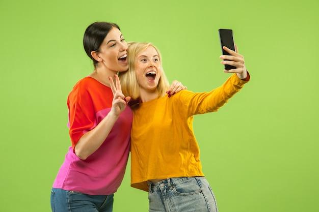 Retrato de chicas muy encantadoras en trajes casuales aislados sobre fondo verde de estudio. novias o lesbianas haciendo selfie. concepto de lgbt, igualdad, emociones humanas, amor, relación.