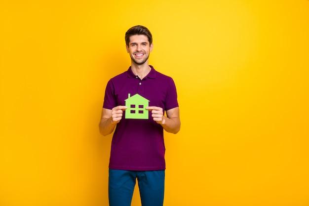 Retrato de chico alegre sosteniendo en manos figura de casa de papel verde aislado
