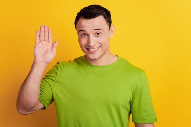 Retrato de un chico amable sonriendo gesto de saludo de mano de onda de sonrisa sobre fondo amarillo