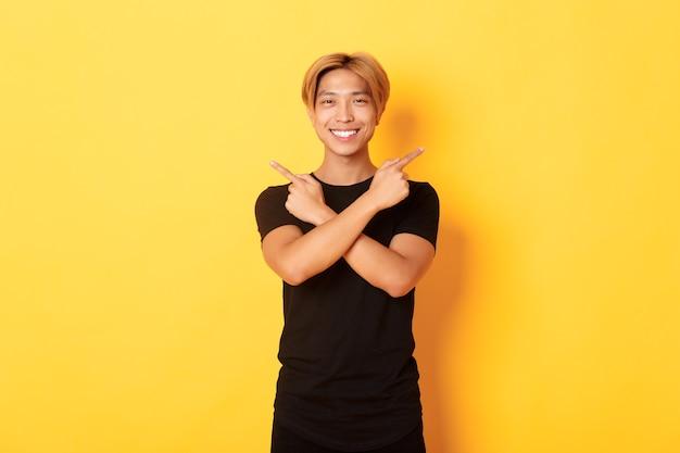 Retrato de chico asiático rubio decidido guapo, estudiante apuntando con el dedo hacia los lados, mostrando dos variantes, pared amarilla de pie.