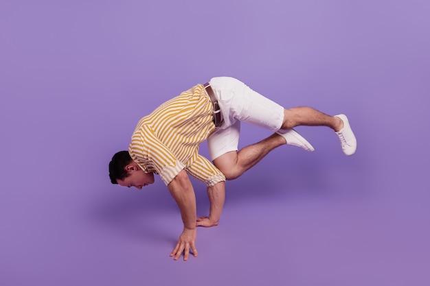 Retrato de chico bailarín moderno baile hip hop movimiento fresco permanecer manos sobre fondo púrpura