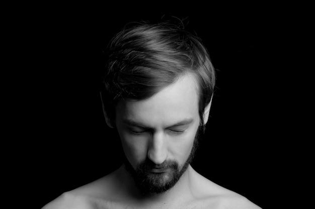 Retrato de un chico con barba sobre un fondo negro