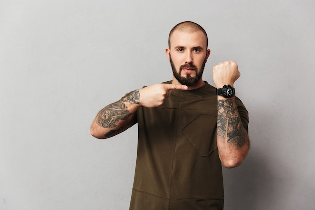 Retrato de chico calvo serio en camiseta casual mirando y señalando con el dedo en su reloj de pulsera, aislado sobre la pared gris