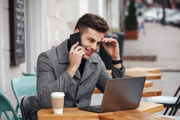 Retrato de chico contento bebiendo café para llevar en la cafetería de la calle, trabajando con un cuaderno y teniendo una conversación móvil