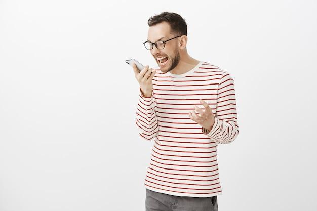 Retrato de chico enojado cabreado con cerdas en gafas negras, gritando al teléfono inteligente y agitando el puño
