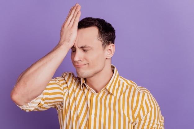 Retrato de chico estúpido golpeó la palma de la cabeza, olvídese de cometer un error sobre fondo púrpura