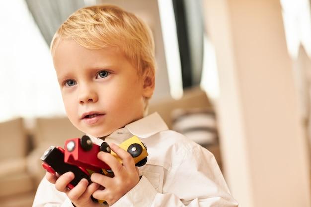 Retrato de chico europeo rubio guapo posando en el interior de la elegante sala de estar con camisa blanca disfrutando de juegos de interior jugando coloridos carros o coches. creatividad, imaginación y fantasía