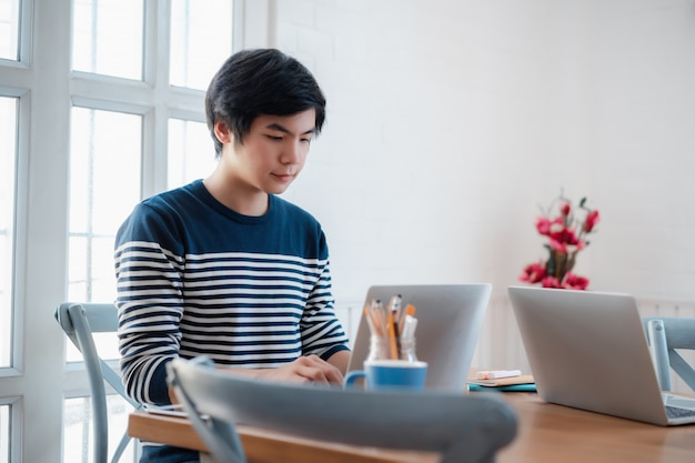 Retrato de chico guapo alegre trabajando en casa.
