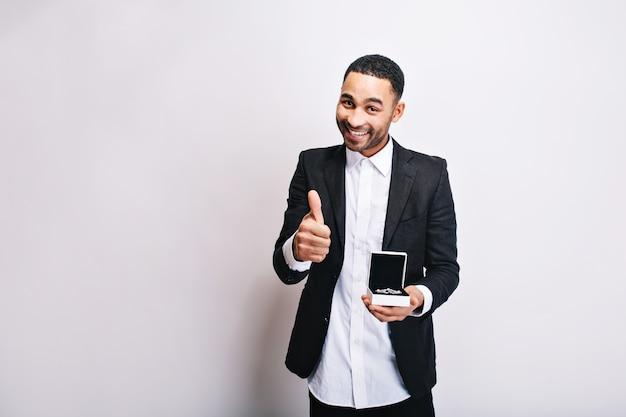 Retrato chico guapo lindo en camisa blanca, chaqueta negra con regalo en manos sonriendo. expresar verdaderas emociones positivas, estado de ánimo alegre, regalo para novia, joyas.
