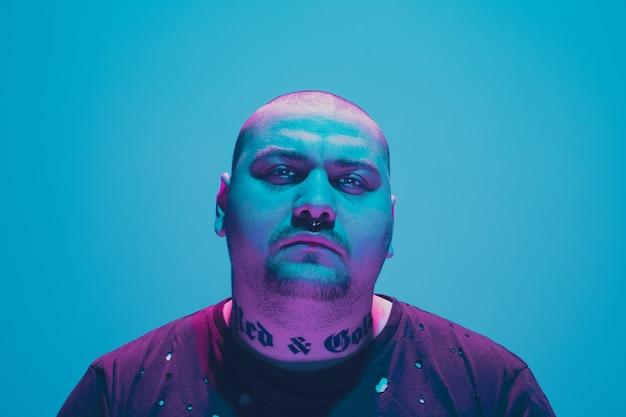 Retrato de un chico hipster con luz de neón de colores sobre fondo azul.