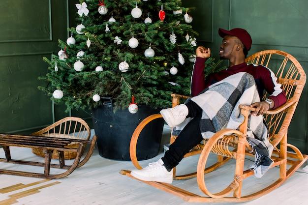 Retrato de un chico inconformista afroamericano vestido con un suéter de lana roja y gorra roja sentado en una silla cómoda cerca del árbol de navidad