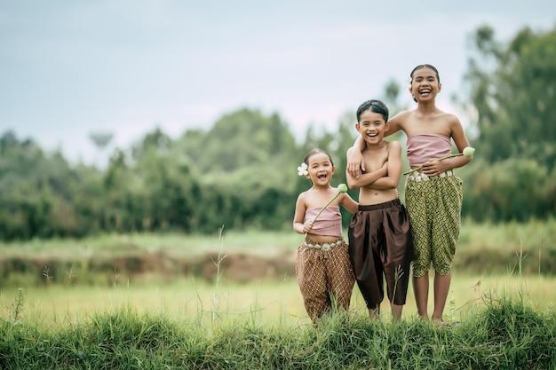 Retrato de chico lindo sin camisa de brazos cruzados y dos chicas encantadoras en traje tradicional tailandés ponen hermosa flor en su oreja de pie en el campo de arroz, riendo, espacio de copia