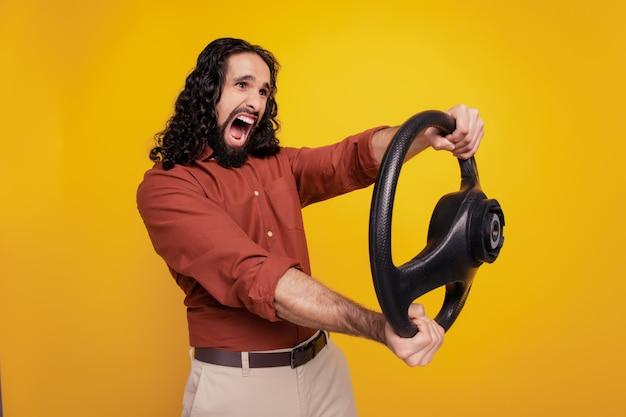 Retrato de chico loco conductor descuidado mantenga el volante grito sobre fondo amarillo